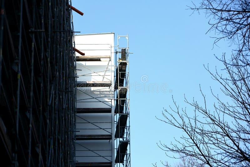 Stålmaterial till byggnadsställning som används för façaderenoveringarbeten arkivbild