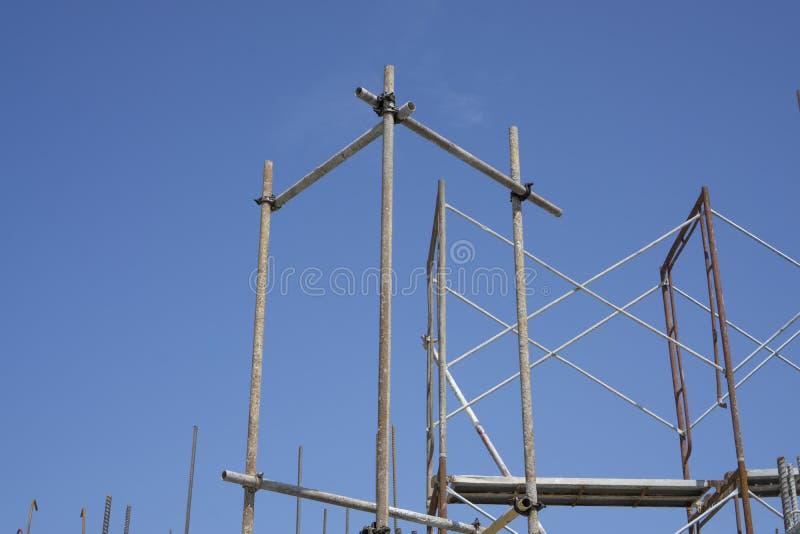 Stålmaterialet till byggnadsställning med brun rost som står på det bästa golvet av byggnaden under blå himmel royaltyfri foto