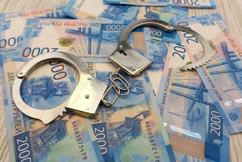 Stålpolisen handfängslar att ligga på bakgrunden av dollar med den vikta bunten av sedlar av ryssrubel royaltyfria foton