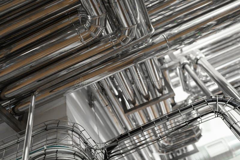 Stålrörledningar och kablar i fabriksinre som bakgrundsbegrepp för farmaceutisk bransch royaltyfria bilder