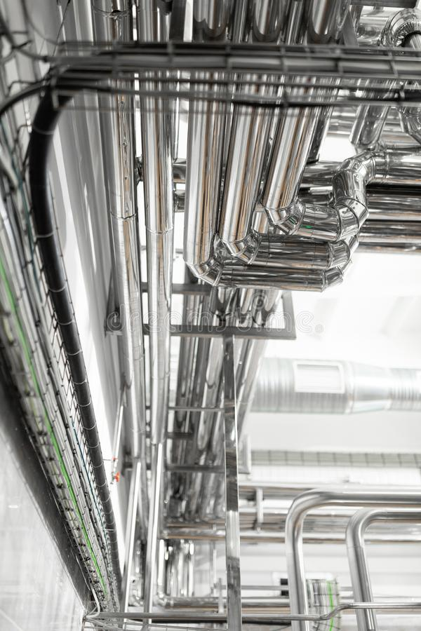 Stålrörledningar och kablar i fabriksinre som bakgrundsbegrepp för farmaceutisk bransch arkivfoton