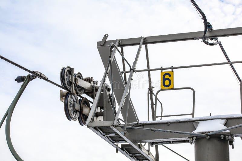Stålrep över hjul i mekanism ovanpå stöttepelaren för skidstolslyftar, nummer 6 på gul platta, ljussken bakgrund fotografering för bildbyråer