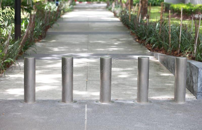 Stålsätta barriären på trottoaren i parkera royaltyfri foto