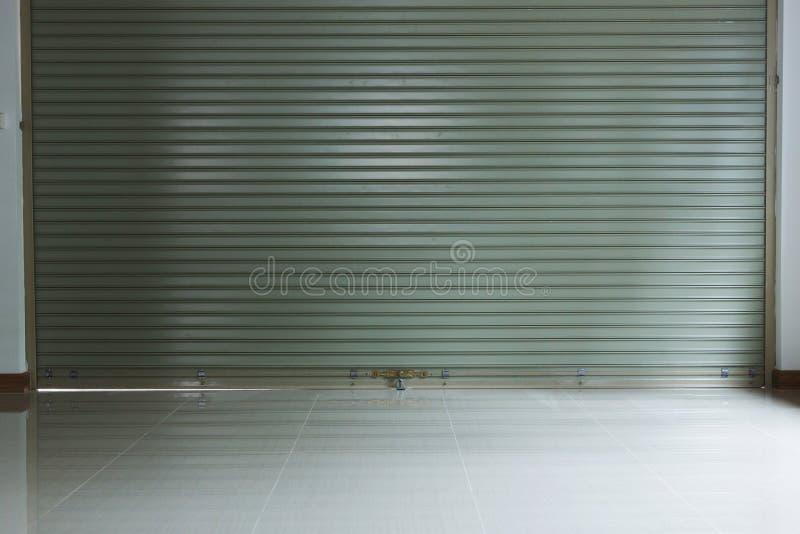 Stålsätta metalldörren, rullslutaredörren och tegelplattagolvet arkivbild