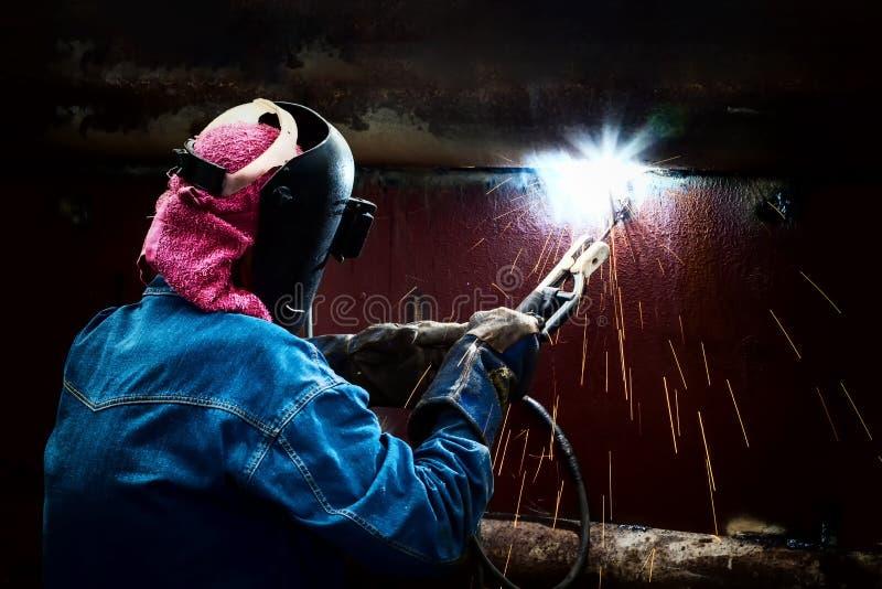 Stålsätta welderen med svetsningmetall och gnistor för skyddande maskering royaltyfri bild