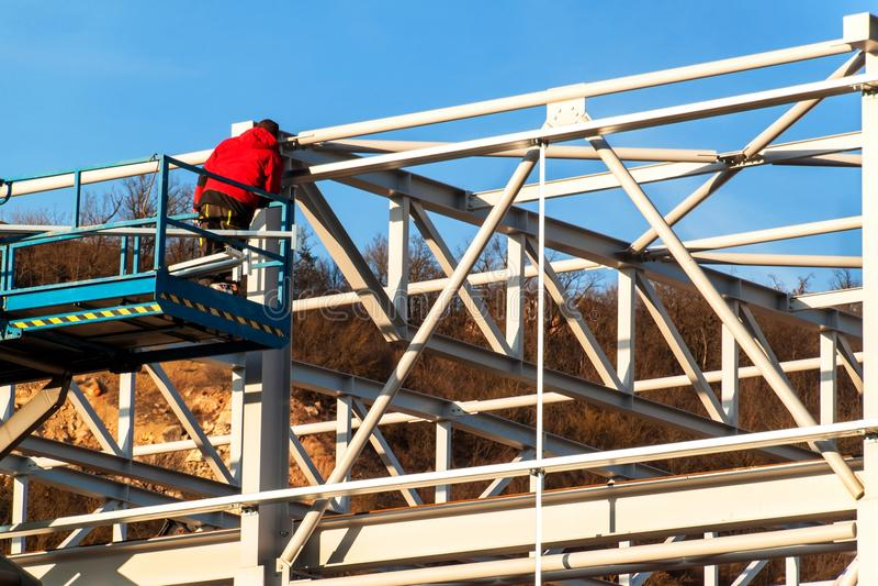 Stålstrukturen är under konstruktion Installation av metallkorridorer Arbete på höjd En solig dag på en konstruktionsplats royaltyfri foto