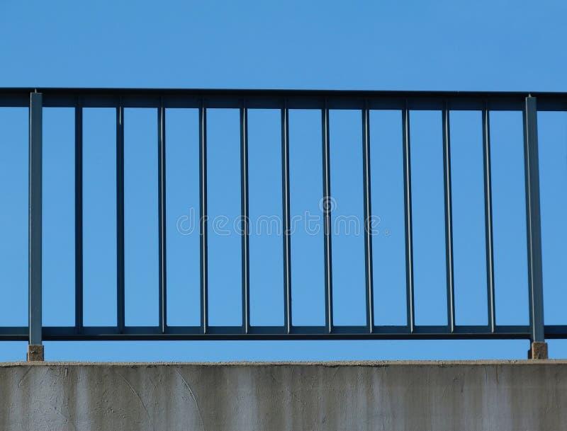 Stålvaktstång med posteringar och stolpar på huvudvägen med blå himmel arkivfoton