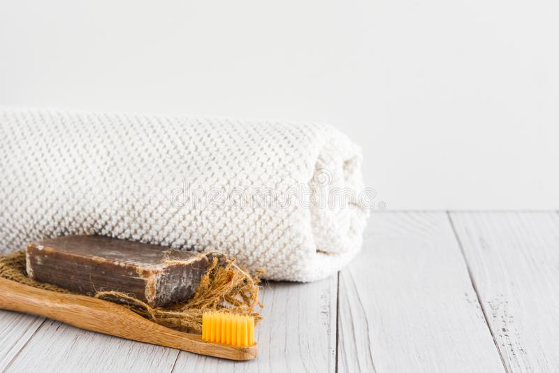 Stång av naturlig handgjord organisk tvål, bambutandborsten och och den vita handduken på vit bakgrund, tomt utrymme för text royaltyfri fotografi