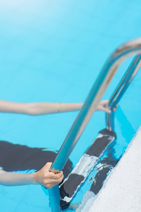 Stång för hastigt grepp för handkvinnahåll i simbassäng arkivfoto
