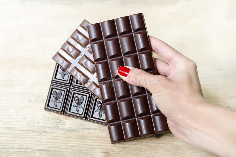 Stången av mjölkar, svart och porös choklad i en hand för kvinna` s som en fan Värme signalen, träbakgrund arkivbilder