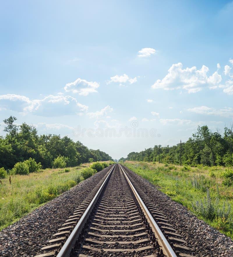 stångväg till horisonten i grönt landskap under blå himmel med moln royaltyfri foto