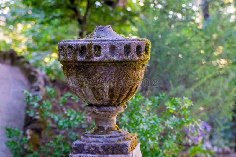 Står dekorativ garnering för trädgården bland grönskan, en forntida granitvas på en sockel i parkerar royaltyfria bilder
