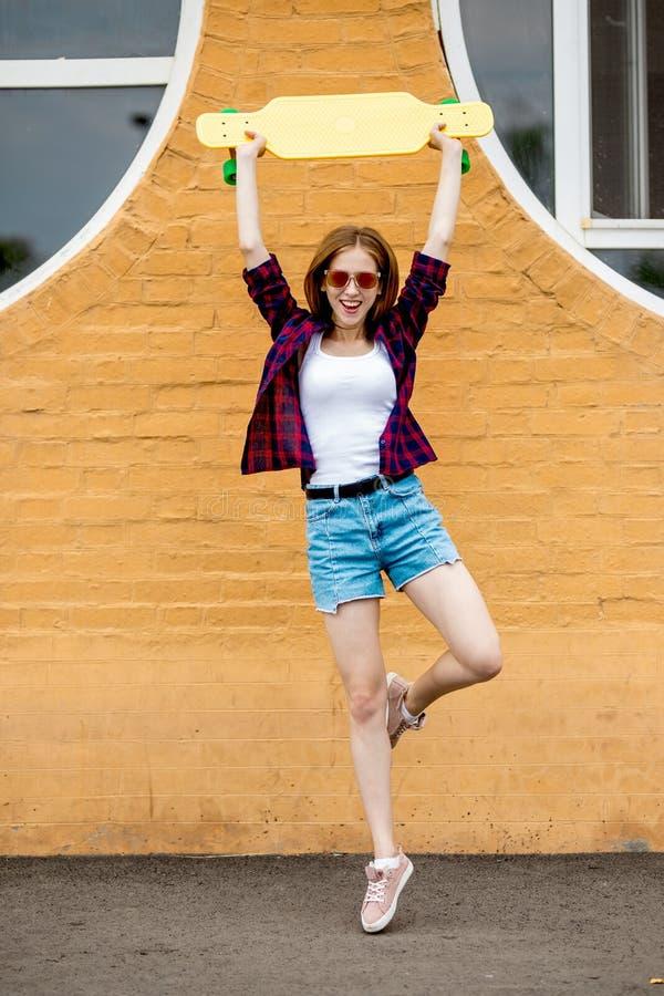 Står den nätta blonda le bärande solglasögon för en flicka, den rutiga skjortan och grov bomullstvillkortslutningar på ett ben fr arkivbild