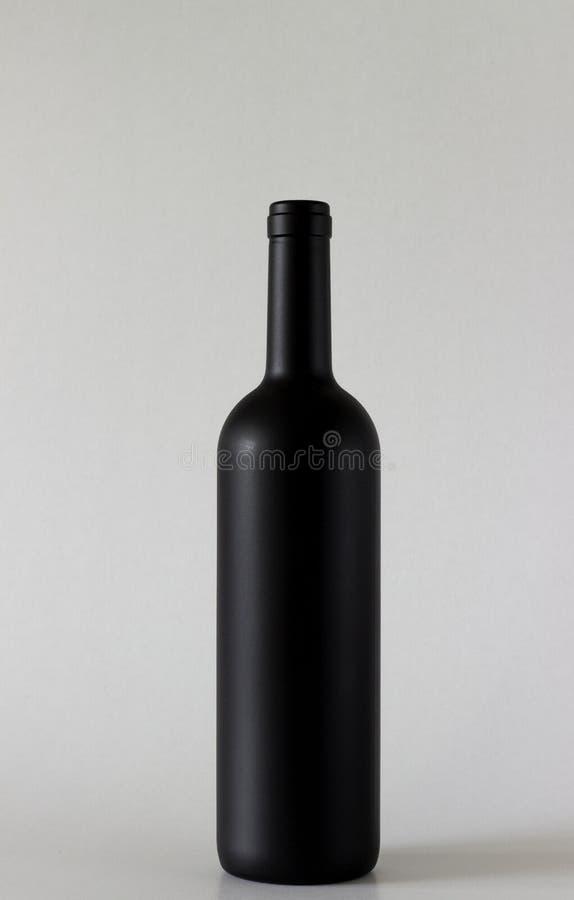 Står den svarta flaskan för vin på grå bakgrund royaltyfri fotografi