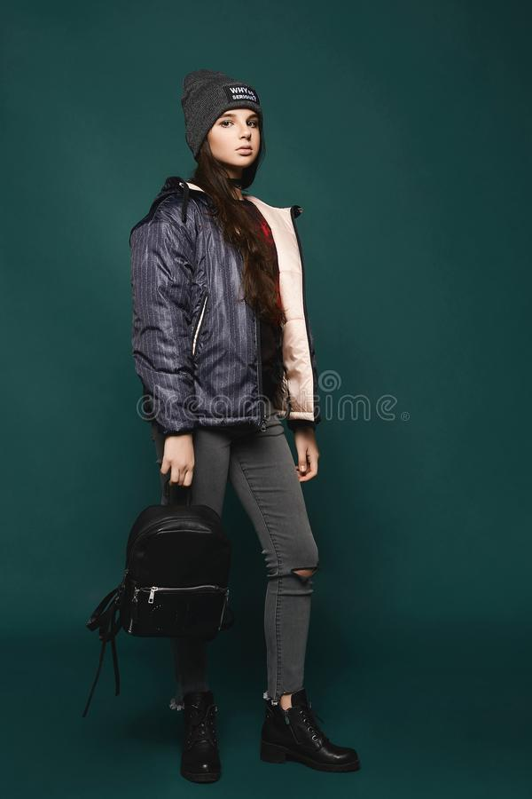 Står den tonåriga flickan för den unga brunetten, i omslag och hatt med en påse, hellång över mörker-gräsplan bakgrund, arkivbilder