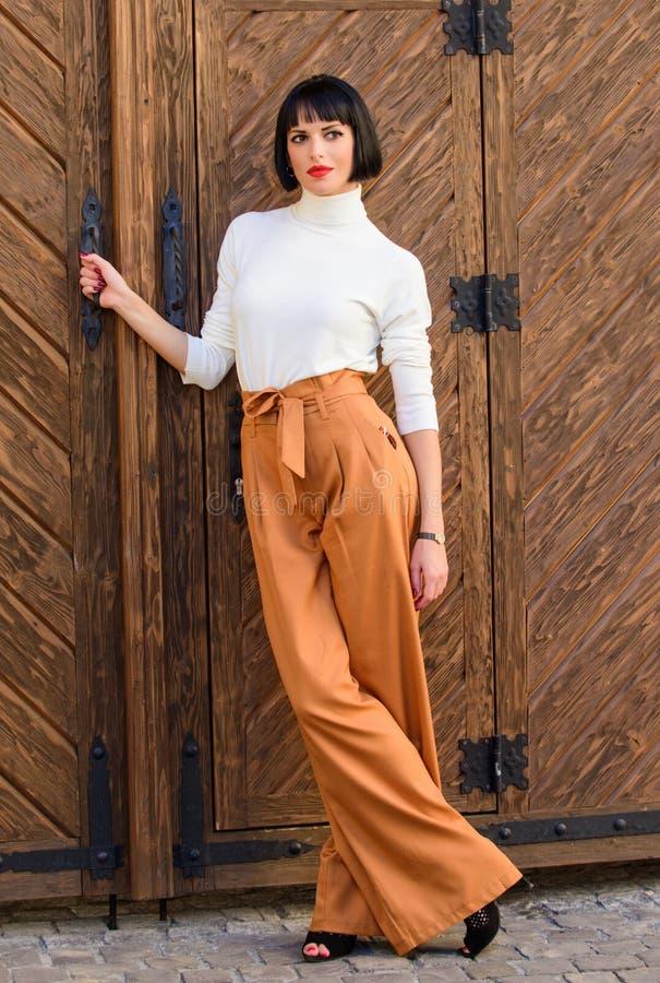 Står den trendiga brunetten för kvinna utomhus träbakgrund mode- och stilbegrepp Flicka med makeup som in poserar royaltyfri fotografi