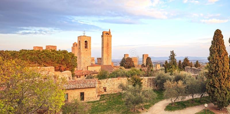 Står hög parkerar den medeltida townen för den San Gimignano landmarken på solnedgång, och. royaltyfri bild