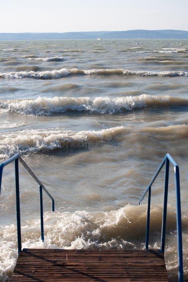 Står i sjön Balaton i stormigt väder med vågor royaltyfri foto