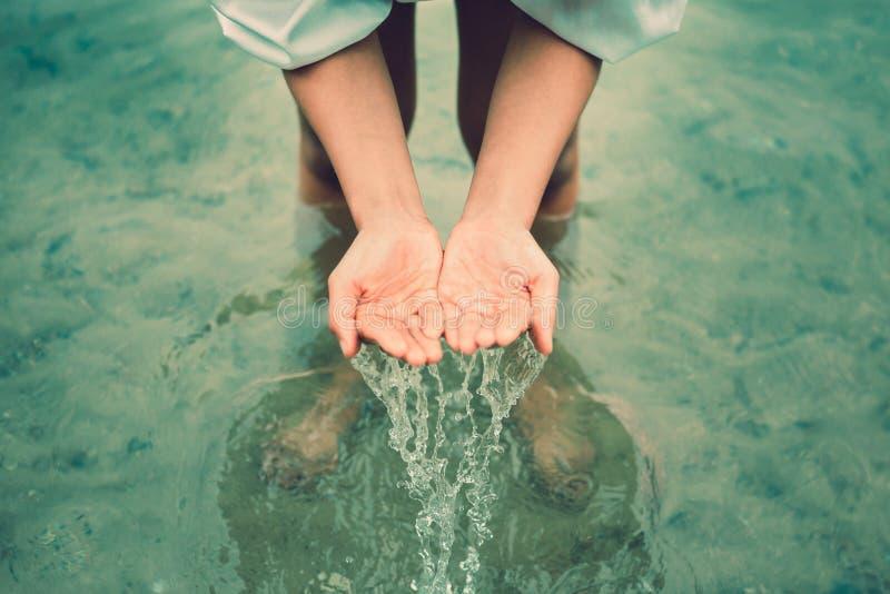 Står kvinnor i vattnet, och händer hämtar vatten och att ha vattenfärgstänk royaltyfria foton