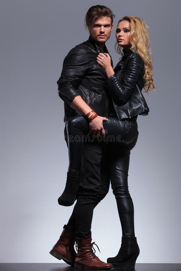 Står ser iklätt läder för par omfamnat och bort royaltyfria foton