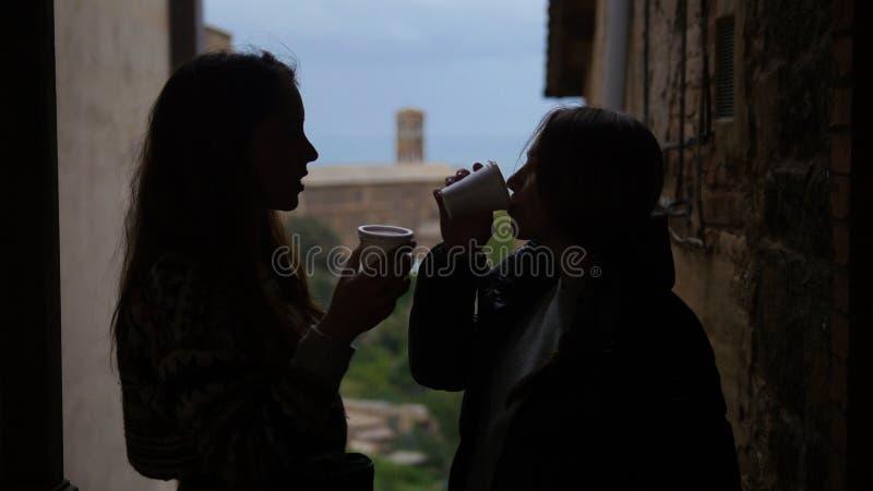 Står silhoettes av två unga kvinnor på balkongen - dricker kaffe och samtal arkivfoto