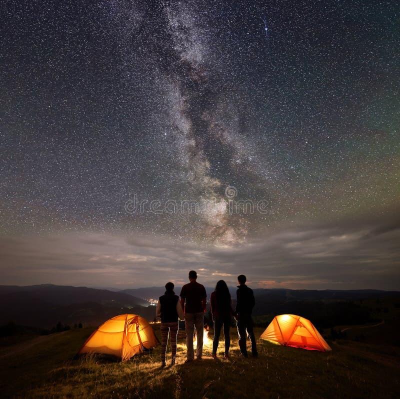Står unga par för bakre sikt två på natten i tältläger tycka om stjärnklar himmel, den mjölkaktiga vägen, berg och den lysande st arkivfoto