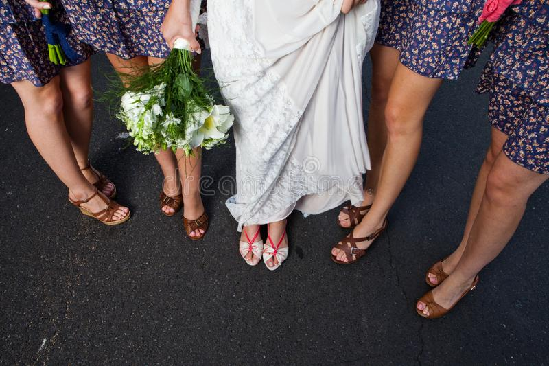 Står visar brud- damer för ett parti på en väg och deras skor royaltyfria bilder