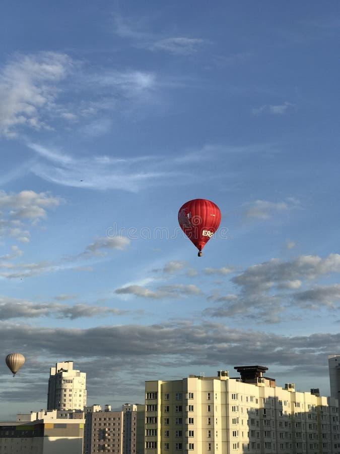 Ståta av ballonger över staden Aerostats av olika färger flyger i den blåa himlen ovanför husen arkivfoton