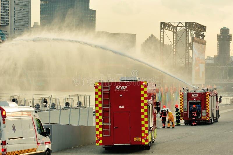 Ståtar motorn för skum för tryckluft för styrka Singapore för borgerligt försvar som (SCDF) besprutar vattenstrålar under nationel arkivbild