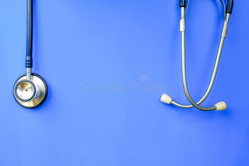 Stéthoscope accrochant au-dessus de l'idéal bleu de fond pour le concept médical et de soins de santé image libre de droits