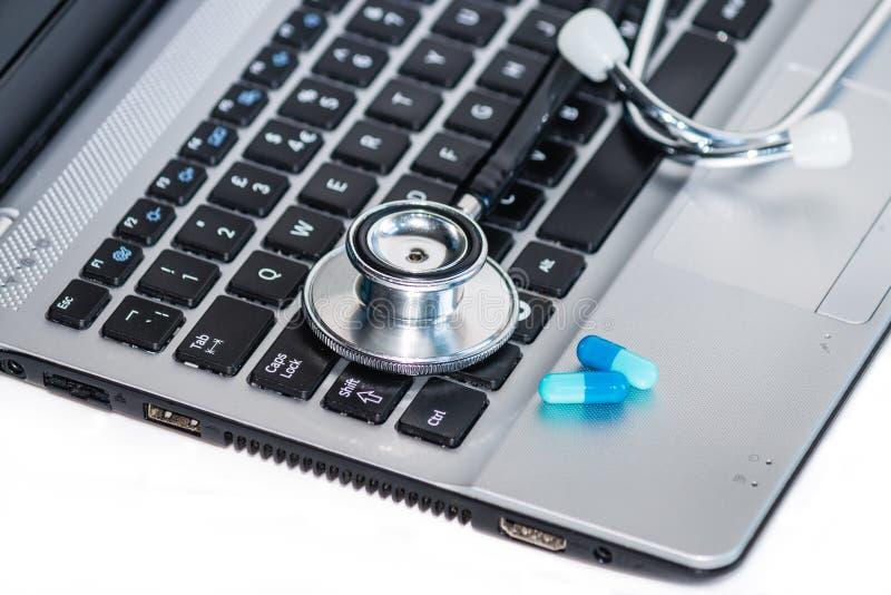 Stéthoscope avec des pilules sur le clavier d'ordinateur portable images libres de droits