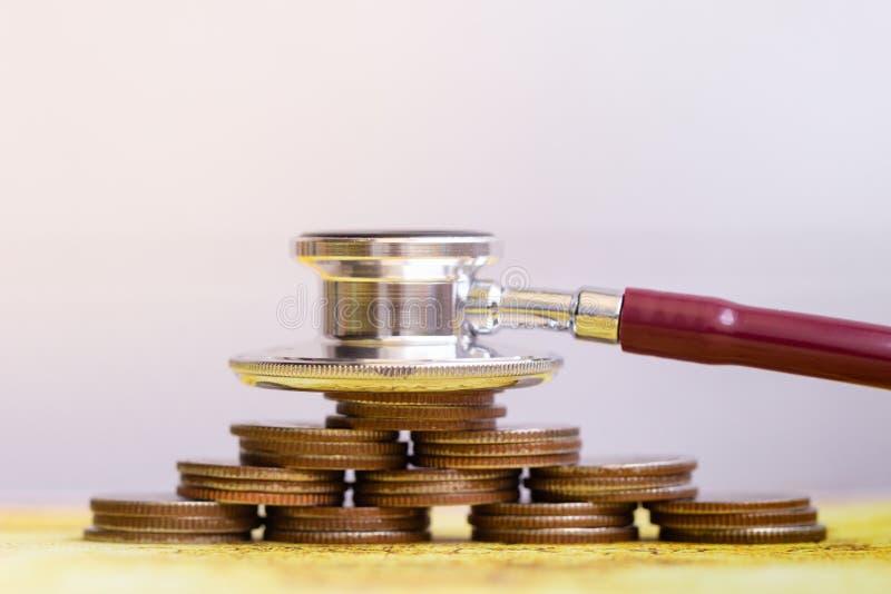 Stéthoscope avec la pile de pièces de monnaie sur le fond blanc augmentation médicale de coût image libre de droits