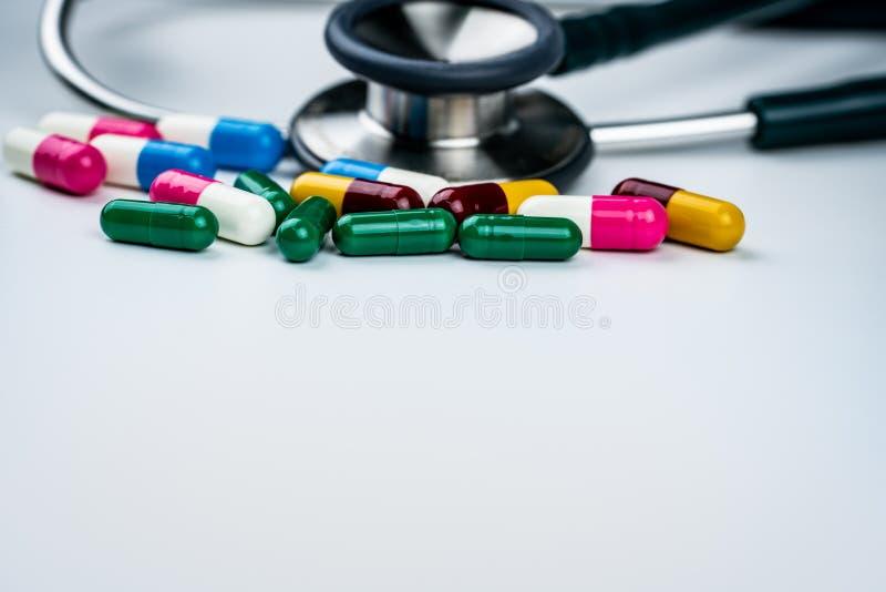 Stéthoscope avec la pile des pilules antibiotiques de capsule sur le fond blanc Résistance au médicament et abus antimicrobiens m images libres de droits