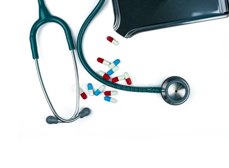 Stéthoscope avec la pile des pilules antibiotiques de capsule sur la table blanche près du plateau de drogue Résistance au médica photos stock