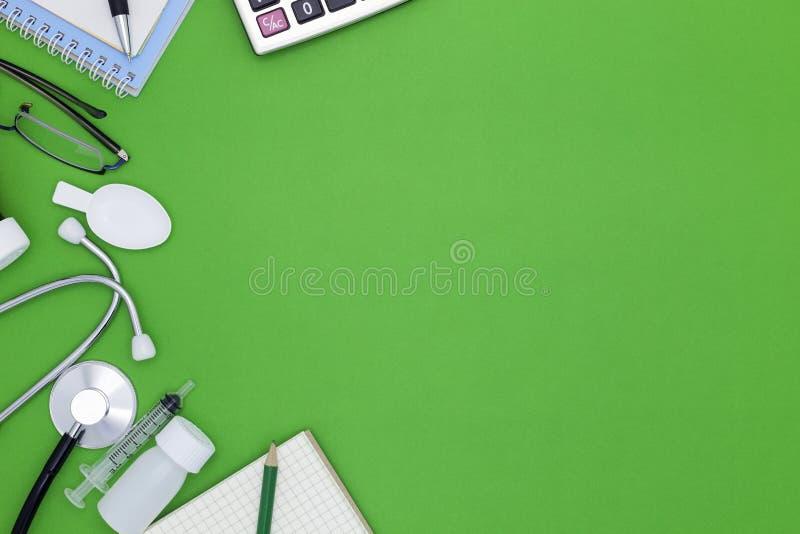 Stéthoscope avec le carnet, stylo, livre blanc, verres, bouteille de médecine, seringue de alimentation sur le fond vert, fond mé photos stock