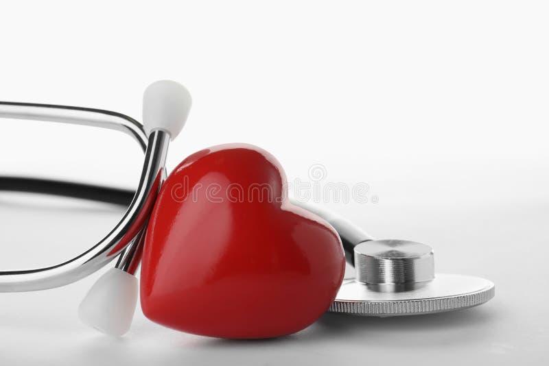Stéthoscope avec le coeur sur le fond blanc image stock