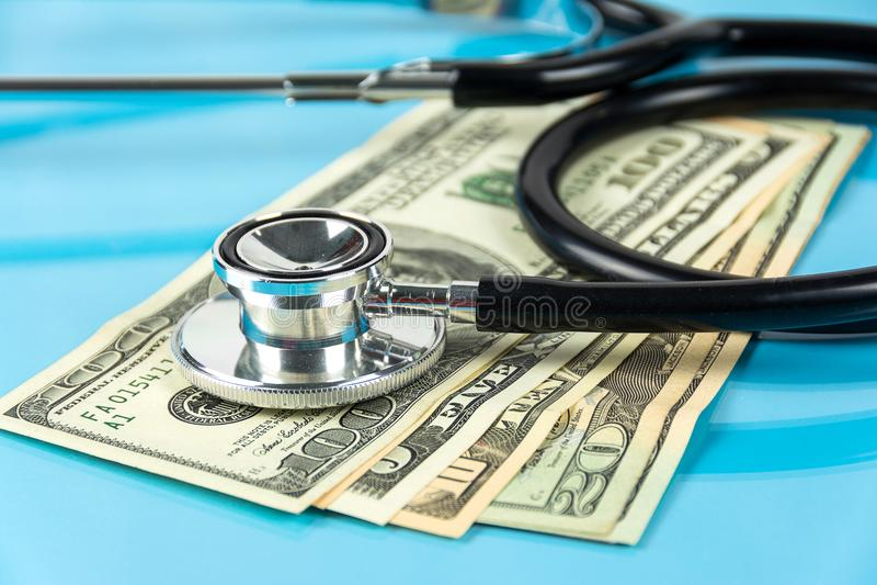 Stéthoscope avec le dollar d'argent sur le fond bleu images stock