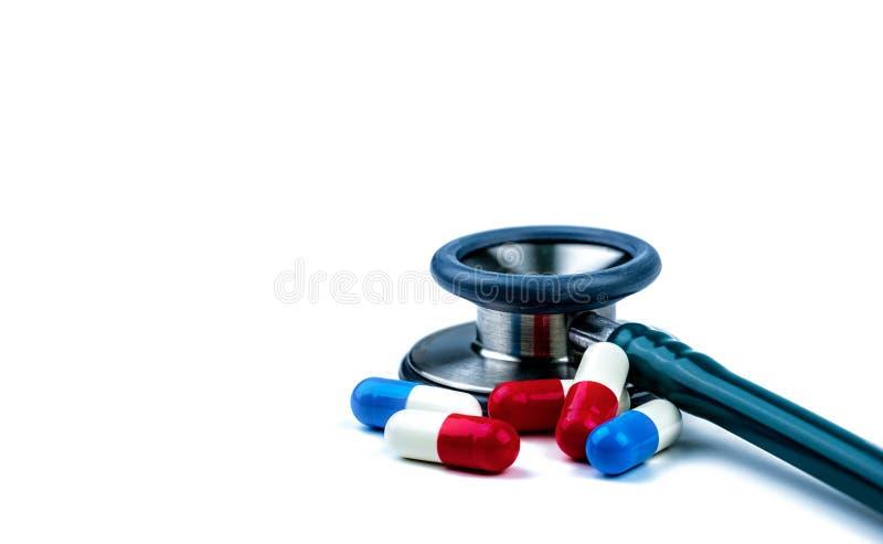 Stéthoscope avec les pilules antibiotiques rouges et bleues de capsule sur la table blanche Résistance au médicament et abus anti photo libre de droits