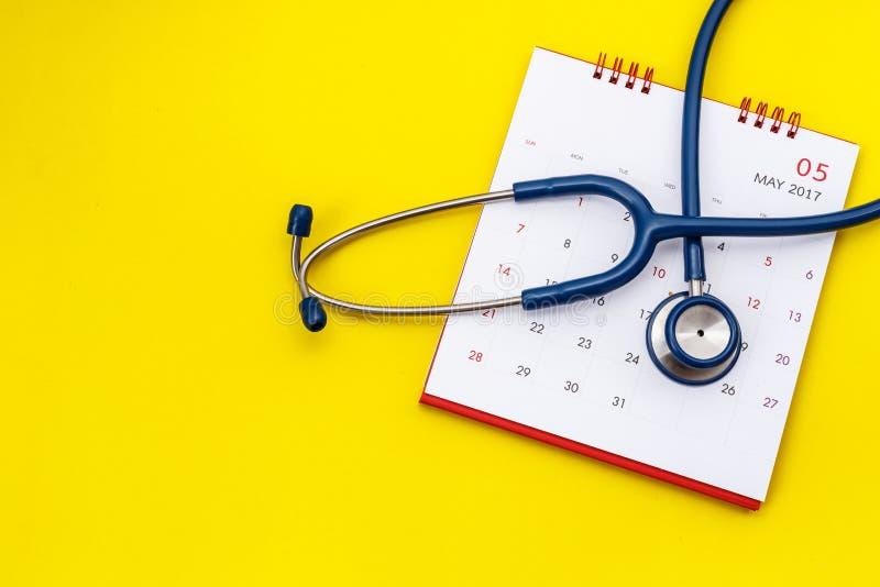 Stéthoscope bleu et calendrier blanc sur le fond jaune Schedu images libres de droits
