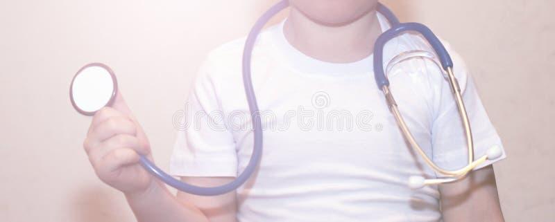 Stéthoscope d'instruments médicaux dans des mains de bébé garçon photographie stock
