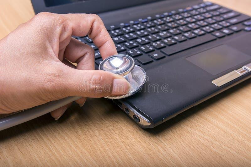 Stéthoscope de prise de main au-dessus de concept d'entretien ordinateur-ordinateur image stock