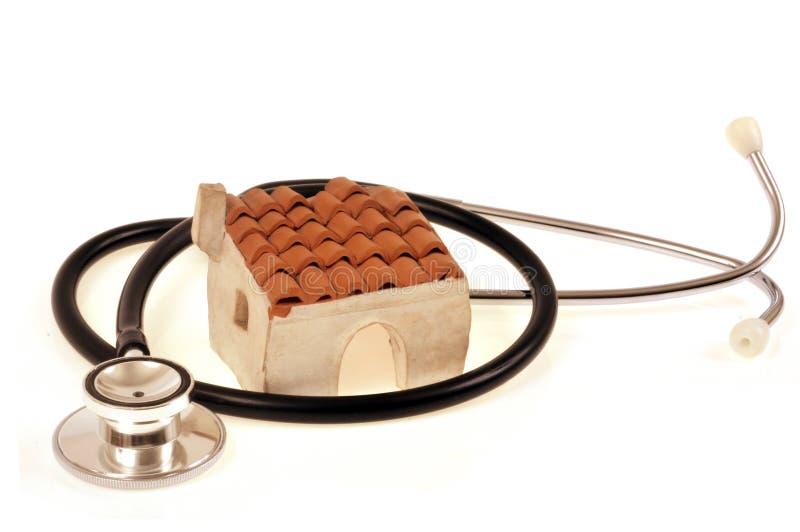 Stéthoscope entourant une fin de petite maison sur le fond blanc image libre de droits