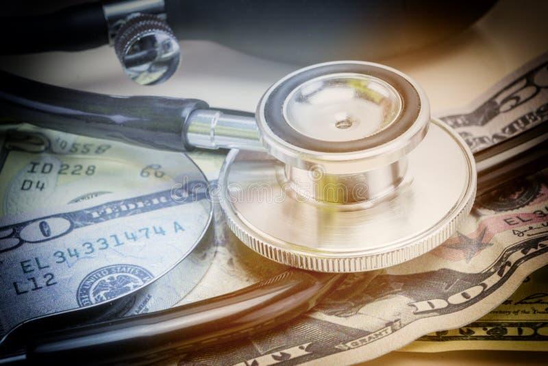 Stéthoscope et argent dans la lumière molle pour l'économie médicale photos stock