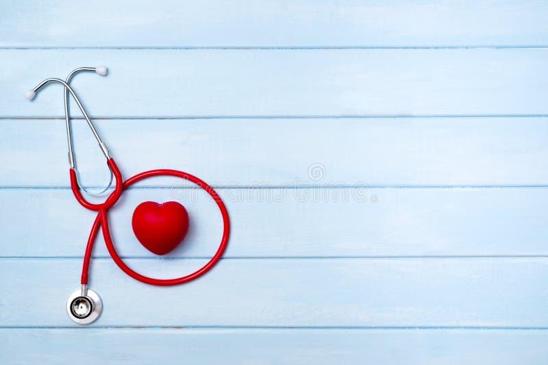 Stéthoscope et coeur rouge sur le fond en bois bleu photographie stock libre de droits