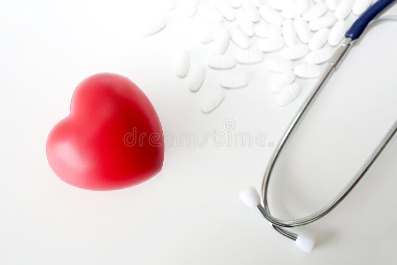 Stéthoscope et coeur rouge sur un fond en bois blanc médecine images stock