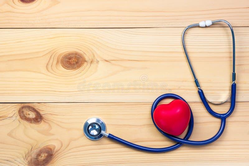 Stéthoscope et forme rouge de coeur sur le fond en bois image libre de droits