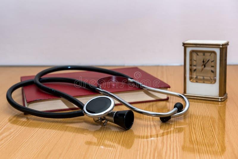 Stéthoscope et livres médicaux se trouvant sur une table photos stock
