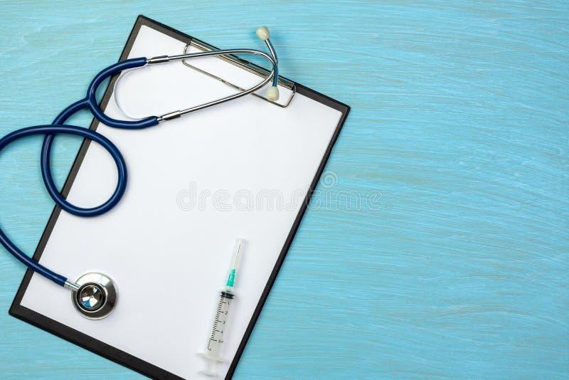 Stéthoscope et seringue sur le presse-papiers avec le papier blanc sur le fond en bois bleu images libres de droits