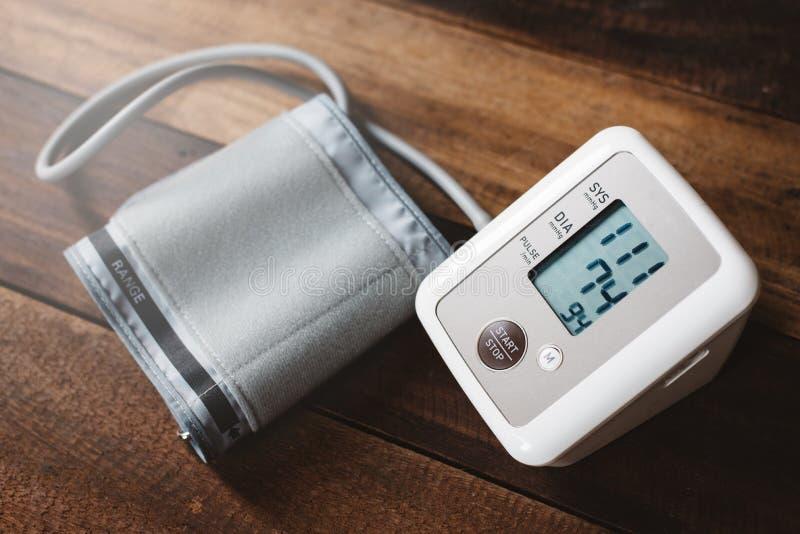 Stéthoscope et Sphygmomanometer un moniteur électronique de tension artérielle sur une table en bois photographie stock