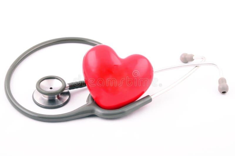 Stéthoscope gris sur la forme rouge de coeur avec le fond blanc images stock